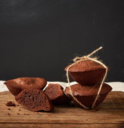 a stack of baked brownie round cakes tied with a rope on a brown wooden board, copy space