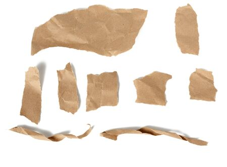 various pieces and twisted brown paper strips and torn pieces isolated on white background, top view 스톡 콘텐츠