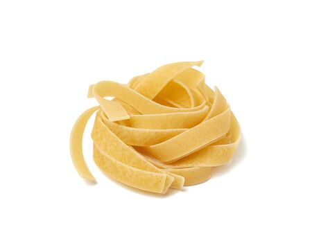 twisted pasta in a round fettuccine nest on a white isolated background, close up