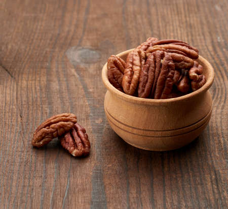 peeled pecans in a wooden plate on the table, close up