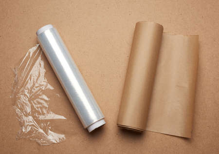 big roll of wound white transparent film for wrapping food and roll of brown craft paper, brown wooden background. rejection of plastic packaging in favor of recyclable materials, plastic rejection concept and eco-friendly, zero waste
