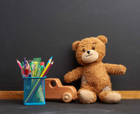 stationery and brown teddy bear sitting on the background of an empty black chalk board, concept back to school
