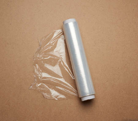 big roll of wound white transparent film for wrapping food, brown wooden background, top view