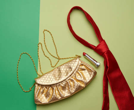 golden fashion handbag on a chain and a red silk tie on a green background, top view Foto de archivo