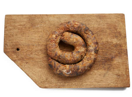 twisted baked homemade meat sausage on a brown wooden background, top view