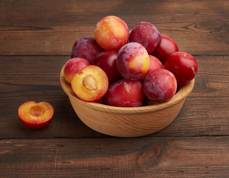 ripe red plums in a round wooden plate on the table, summer harvest