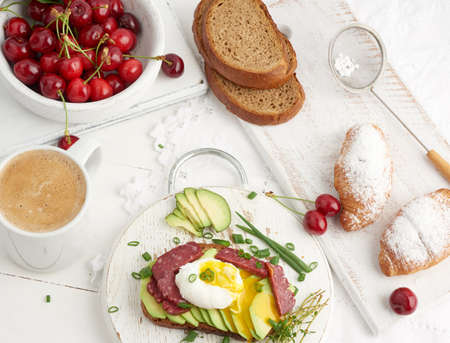 toast with poached egg and avocado on a round board, next to croissants and ripe red cherries, morning breakfast, top view on a white table