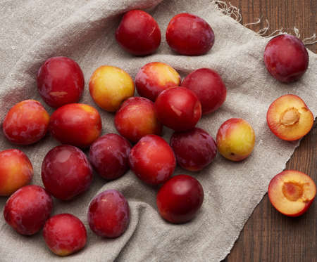 ripe red plums on a gray linen towel, brown wooden table, top view Standard-Bild