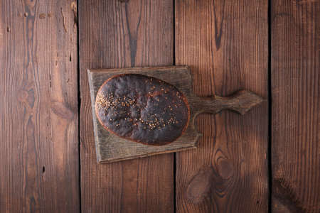 baked rye bread lies flour on a wooden old table, brown background, top view Archivio Fotografico