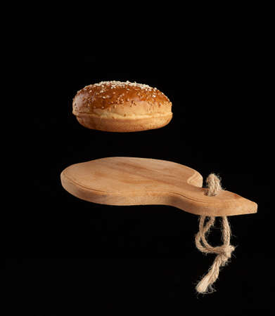 baked round bun with sesame seeds hover over brown wooden cutting board, black background, hamburger ingredient