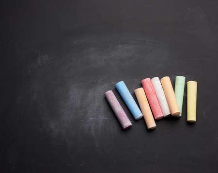 multicolored chalk on lie on empty black chalk board, place for inscription Фото со стока