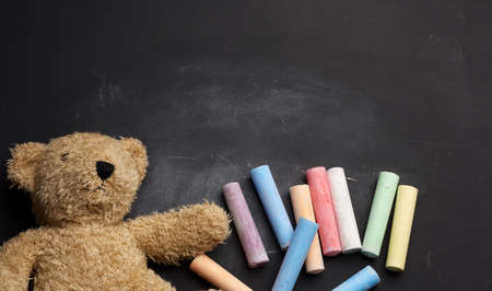 brown teddy bear and colorful crayons on black chalk board, back to school Stockfoto