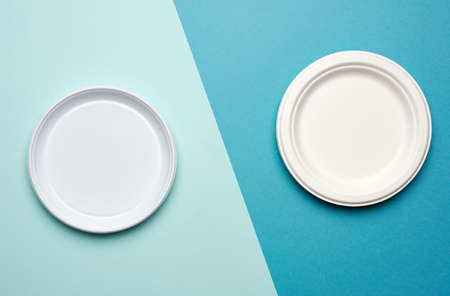 empty white plastic plates and white paper disposable plates on a blue background, top view. The concept of rejection of plastic, environmental conservation