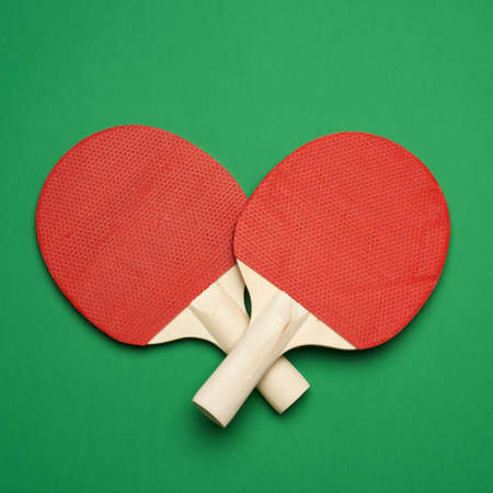 red wooden table tennis racket on green background, pair of ping pong sports tools, top view