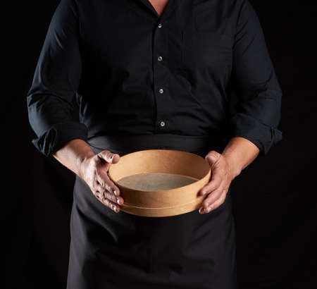 man in black uniform holding empty vintage round wooden sieve for sifting flour, chef stands against black background