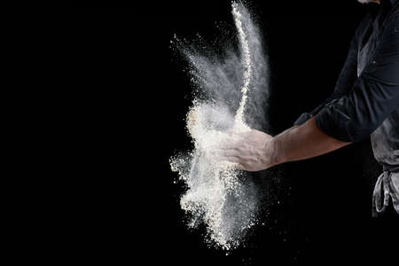 chef in black uniform sprinkles white wheat flour in different directions, product scatters dust, black background, copy space Archivio Fotografico