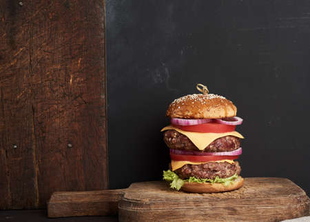 double cheeseburger with tomatoes, onions, barbecue cutlet and sesame bun on an old wooden cutting board, brown background. Fast food Archivio Fotografico