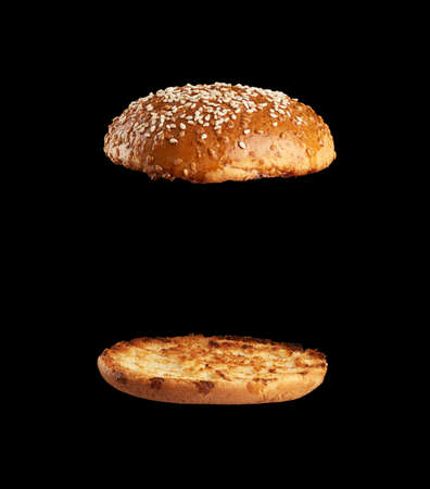 baked sesame seed round bun cut in half, halves fried and levitating in air over each other, black background