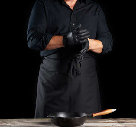 chef in black shirt and apron puts black latex gloves on his hands before preparing food, black background