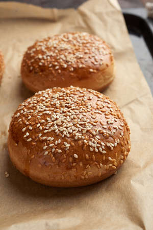 baked sesame buns on brown parchment paper, ingredient for a hamburger, close up Archivio Fotografico