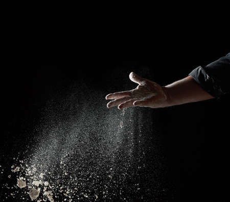 baker's hand throws a handful of white wheat flour on a black background, the particles fly in different directions