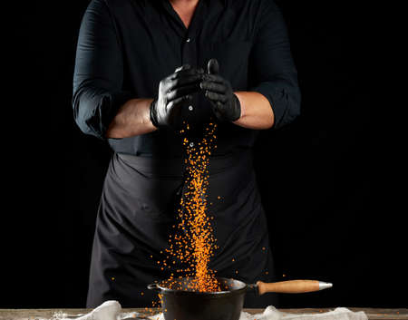 chef in black clothes and latex gloves pours raw lentils into a round cast iron pan with a handle, black background Archivio Fotografico