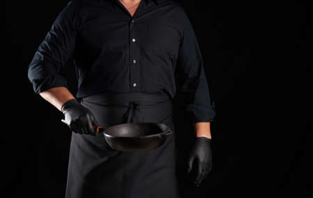 male cook in black uniform and latex gloves holds an empty round vintage black cast iron pan in front of him, low key