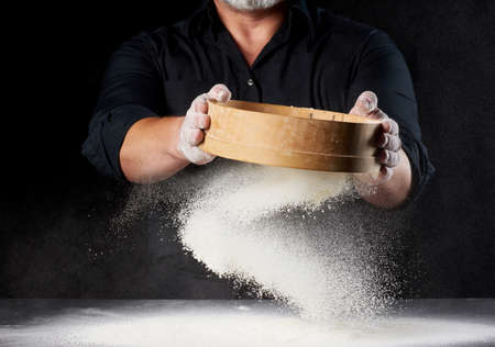 chef a man in a black uniform holds a round wooden sieve in his hands and sifts white wheat flour on a black background, the particles fly in different directions Archivio Fotografico