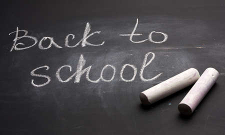 lettering back to school in white chalk on a black school board and a piece of chalk, close up Archivio Fotografico