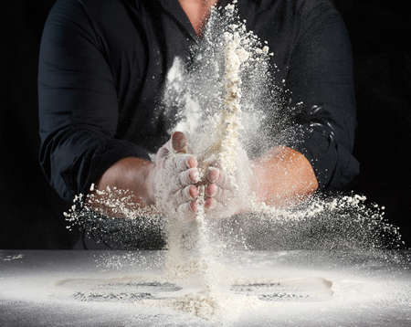 chef in black uniform sprinkles white wheat flour in different directions, product scatters dust, black background, man sitting at a table Archivio Fotografico