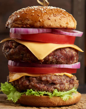 double cheeseburger with tomatoes, onions, barbecue cutlet and sesame bun on an old wooden cutting board. Fast food, close up Archivio Fotografico