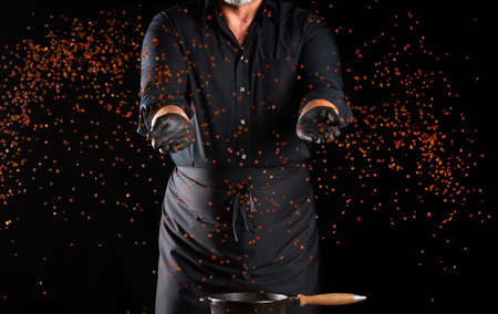 chef in a black uniform throws lentil grains forward on a black background, the product flies in different directions