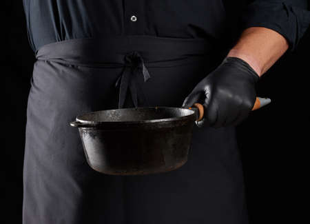 cook in black uniform and latex gloves holds an empty round vintage black cast iron pan in front of him, low key