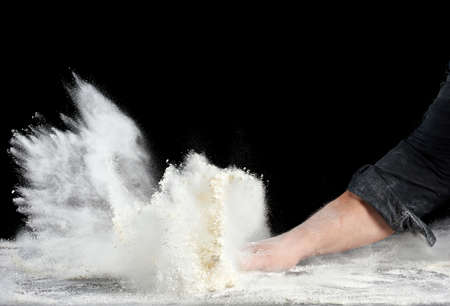 chef in black uniform sprinkles white wheat flour in different directions, product scatters dust, black background, particles scatter and freeze in the air