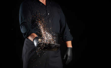 man in a black uniform holding a round cast iron pan with salt and pepper, chef tosses spice up on a black background, copy space