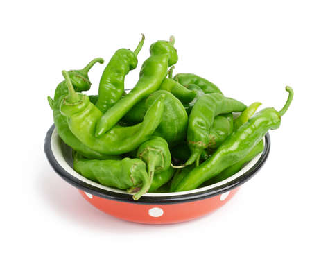 green hot pepper pods in red metal plate isolated on white background, close up