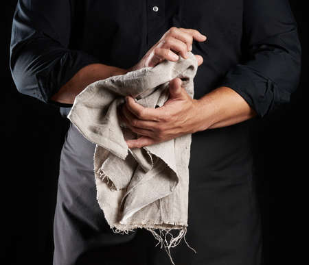 man in black uniform holds gray linen rag and wipes his hands, chef stands on black background, close up