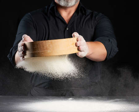 chef a man in a black uniform holds a round wooden sieve in his hands and sifts white wheat flour on a black background, the particles fly in different directions, dusty space