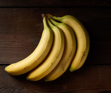 bunch of yellow unpeeled ripe bananas on a brown wooden table, top view