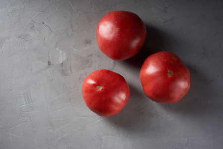 three ripe red tomatoes on a gray background, top view, copy space