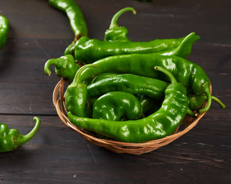 green hot pepper pods in a round wicker basket on a brown wooden table, top view Archivio Fotografico
