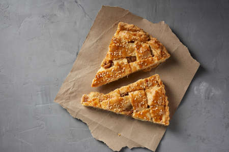 two baked pieces of apple pie on brown paper, top view, gray background Archivio Fotografico