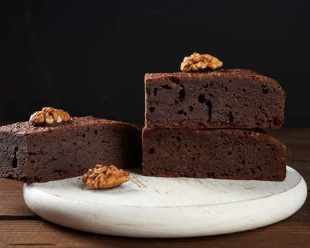 stack of baked pieces of brownie chocolate cake with nuts on a wooden board, delicious dessert