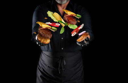 chef in a black shirt, apron and latex black gloves stands on a black background, in his hands flying cheeseburger ingredients: a bun with sesame seeds, cutlet, tomato, lettuce and onion rings, cheese