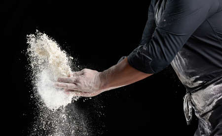 chef in black uniform sprinkles white wheat flour in different directions, product scatters dust, black background, close up Banque d'images
