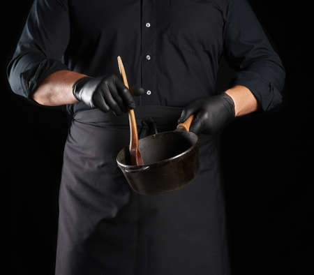 male cook in black uniform and latex gloves holds an empty round vintage black cast iron pan and wooden spoon in front of him, low key 版權商用圖片