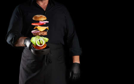 adult man in a black uniform holding a cast iron round frying pan with frozen cheeseburger ingredients: sesame bun, cheese, tomato, onion, meat cutlet, black background, copy space Stok Fotoğraf