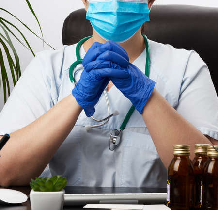 doctor in a white coat and blue latex gloves sits at a white work table in his office, concept of patient reception in the clinic, hands joined in front of the chest, focused pose Zdjęcie Seryjne
