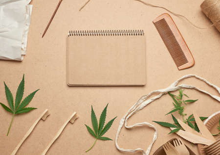 open notebook with empty sheets, a textile bag and disposable tableware from brown craft paper, green hemp leaves on a wooden background. View from above, plastic rejection concept, zero waste