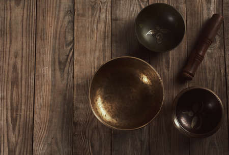 Tibetan singing copper bowl with a wooden clapper on a brown wooden table, objects for meditation and alternative medicine, top view, copy space